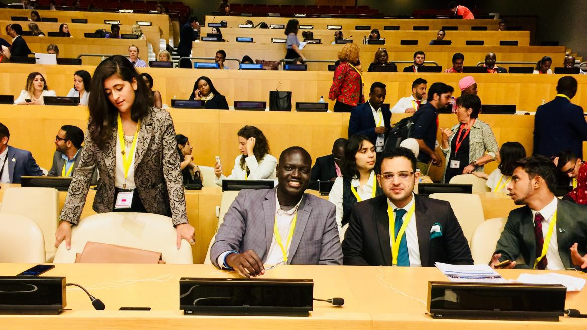 Bandak Lul seated next to youth delegate from Pakistan