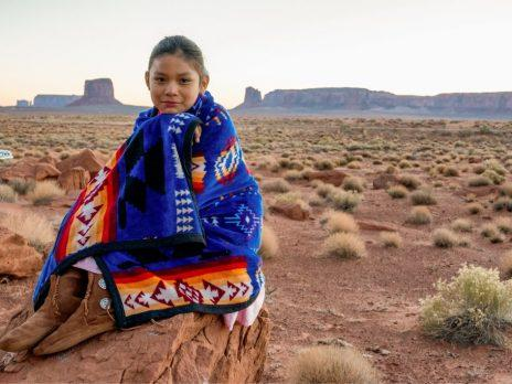 A Native American girl sits outside wrapped in a blanket